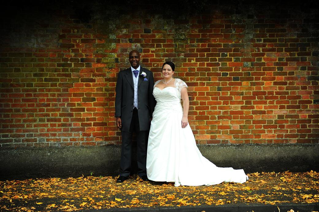 Smiling newly-wed couple standing in front of the wall amongst the leaves in this wedding photo taken at Chalk Lane Hotel in Epsom by Surrey Lane wedding photographers