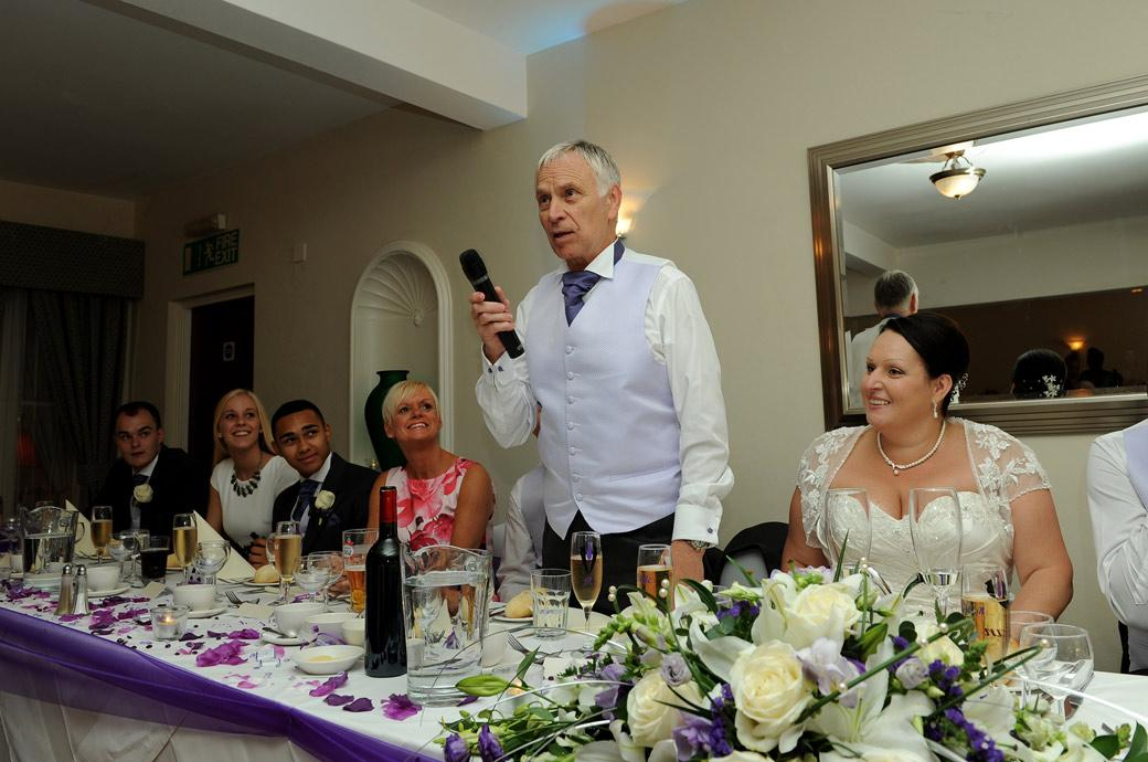 Father of the Bride gets everyone smiling as he starts off the speeches in this fun wedding photograph taken at the relaxed and intimate Surrey wedding venue Chalk Lane Hotel