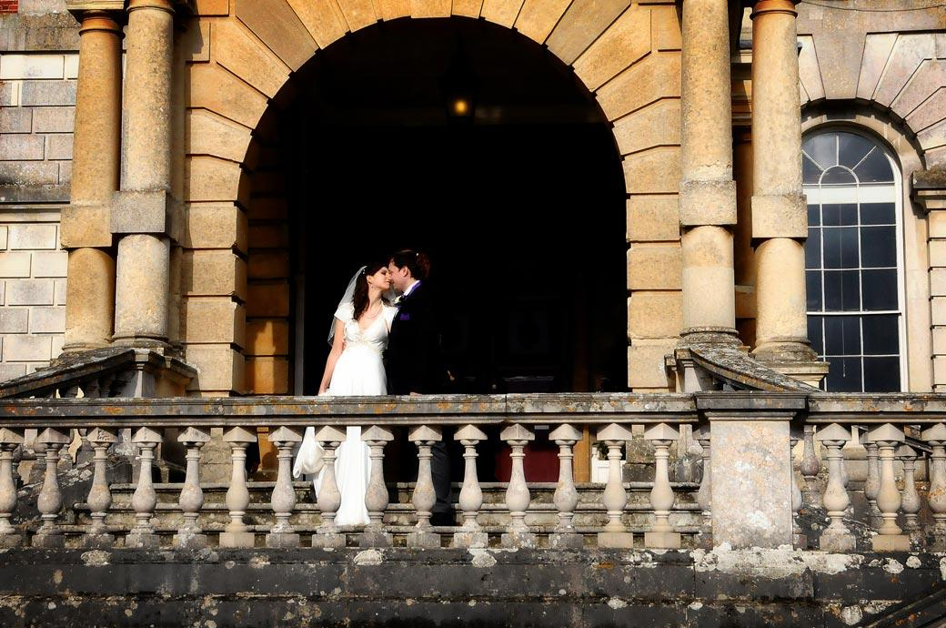 A classic romantic stolen kiss wedding photograph framed by the arch of the main entrance to Clandon Park Surrey by Surrey Lane wedding photographers