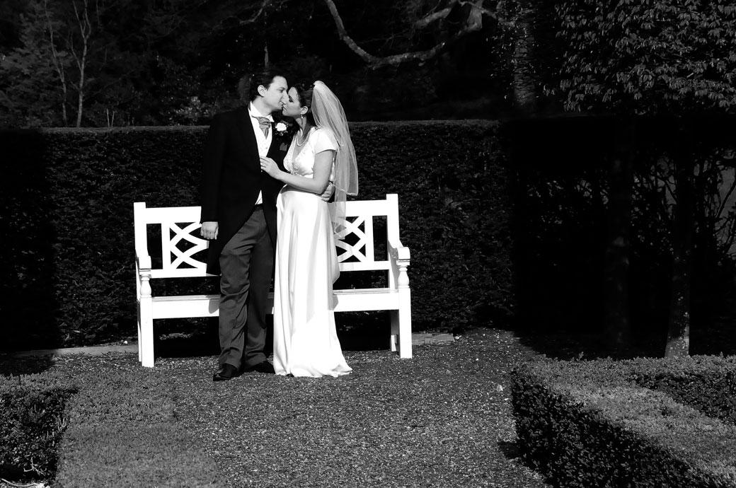 Groom gently pulls his wife close to him for an intimate moment in the beautiful and tranquil Parterre Garden at Clandon Park Surrey wedding venue