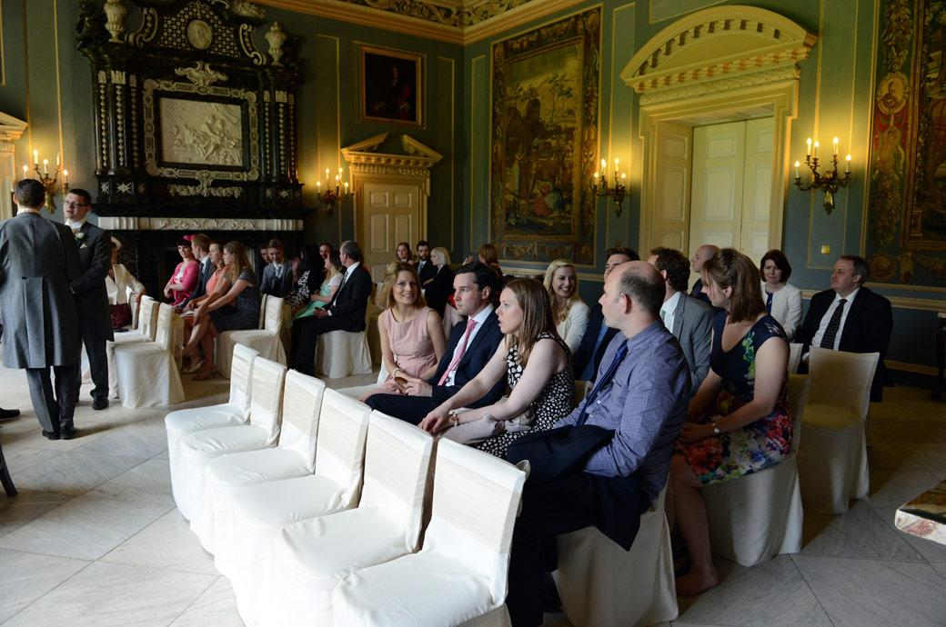 Guests sitting down waiting for the start of the marriage ceremony in this informal wedding picture in the Tapestry Room at Clandon Park Guildford by Surrey Lane wedding photography