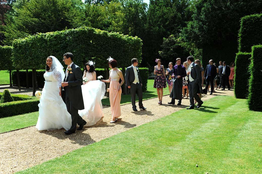 The happy Bride and Groom lead the guests through the colourful Parterre garden in this joyful wedding picture taken at Clandon Park a stunning Surrey wedding venue