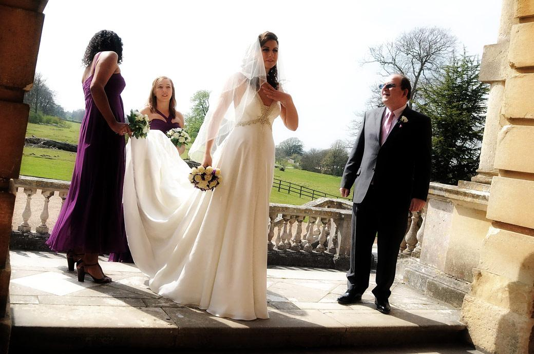 A beautiful, serene Bride waiting excitedly with her bridesmaids captured by Surrey Lane wedding photography outside the main door of Clandon Park