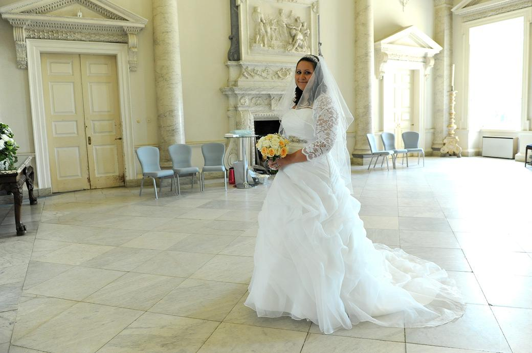 A nervous Bride glances over in this wedding picture taken as she walks alone across the Marble Hall to the Tapestry Room at Clandon Park Guildford a stunning Surrey wedding venue