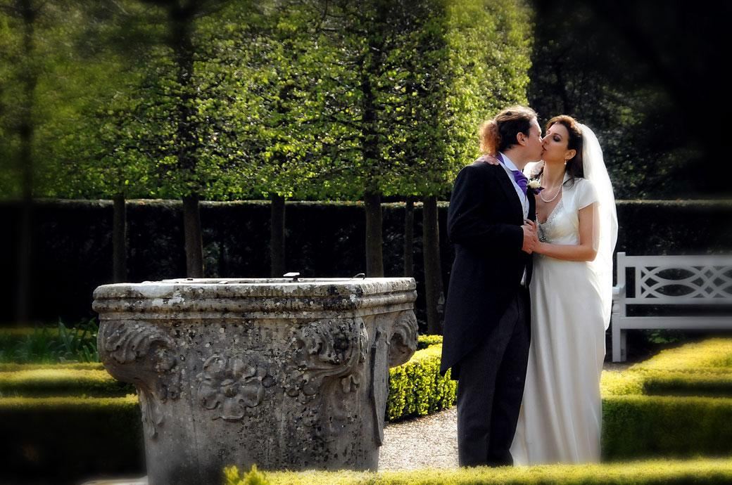 A beautiful Bride passionately kissing her husband in this romantic wedding photograph taken in the Parterre garden at Clandon Park Guildford Surrey