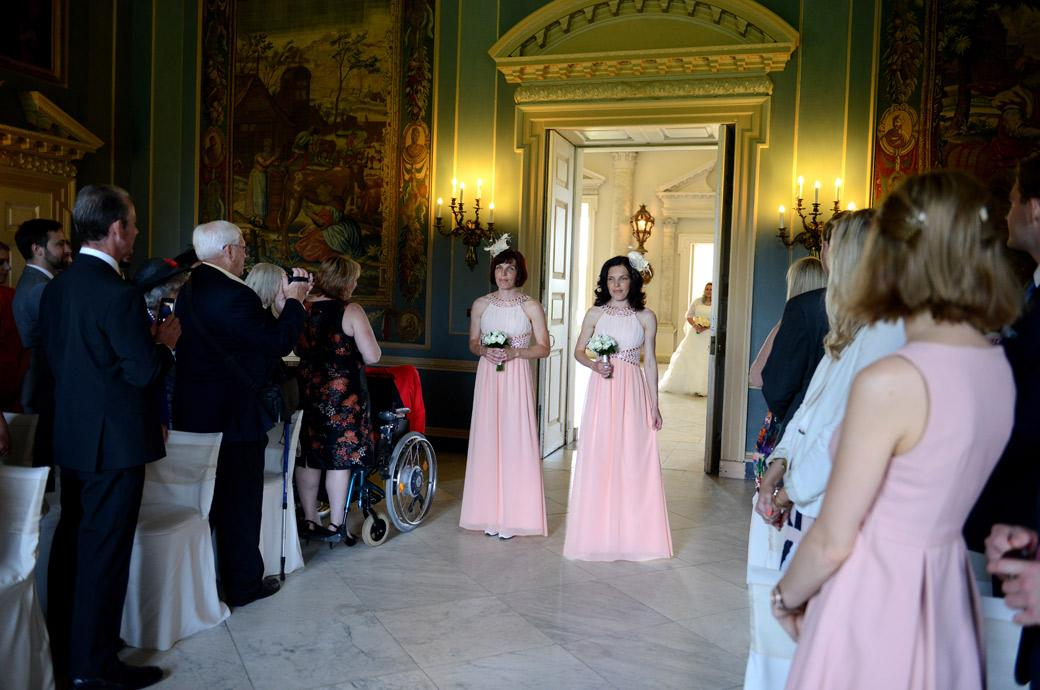 The Bridesmaids walk down the aisle with the Bride following in the Marble Hall in this wedding photograph taken at Surrey wedding venue Clandon Park in Guildford