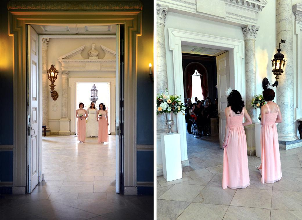 Bridesmaids in pink lead the way across the Marble Hall to the Tapestry Room in this wedding photo at Clandon Park Guildford  taken by Surrey Lane wedding photographers