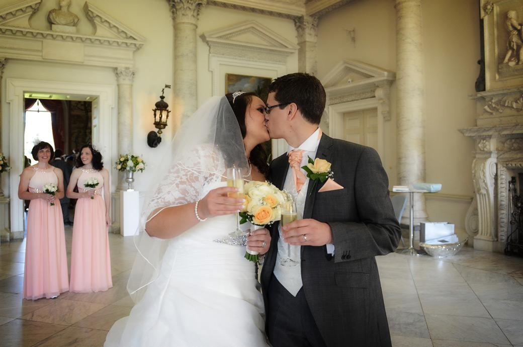 Celebratory champagn and a kiss in this romantic wedding photo taken of the newly-weds in the Marble Hall after their ceremony at Surrey wedding venue Clandon Park Guildford