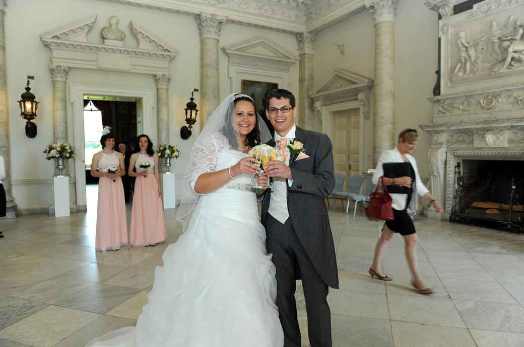 All champagne and smiles as the happy couple clink glasses as husband and wife in this wedding photo from the Marble Hall in Clandon Park by Surrey Lane wedding photography