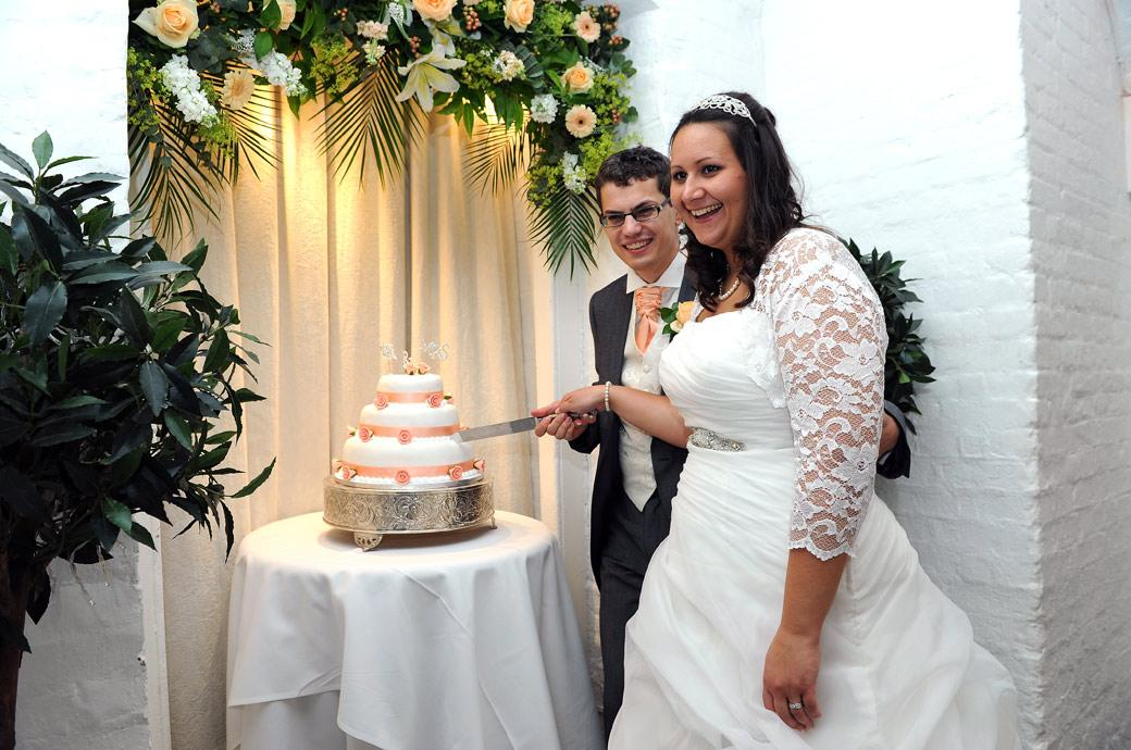 Happy couple all smiles as they pose cutting the cake in this fun wedding photo taken at the magnificent Surrey wedding venue Clandon Park