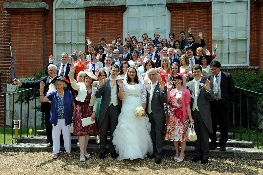 Waving from the steps in this everyone group wedding photograph captured by Surrey lane wedding photographers at the wonderful Clandon Park Surrey wedding venue