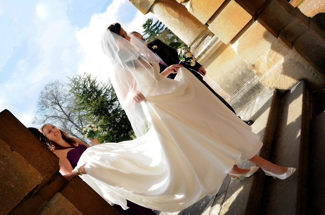Excited Bride holds up her dress as she descends the steps to enter the Marble Hall at  Clandon Park a wonderful Surrey wedding venue in  Guildford