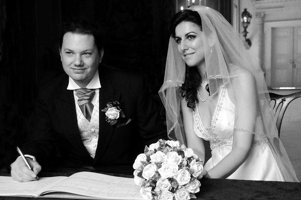A wedding photograph taken at Clandon Park of a beautifully serene Bride watching her husband sign the wedding register by Surrey Lane wedding photography