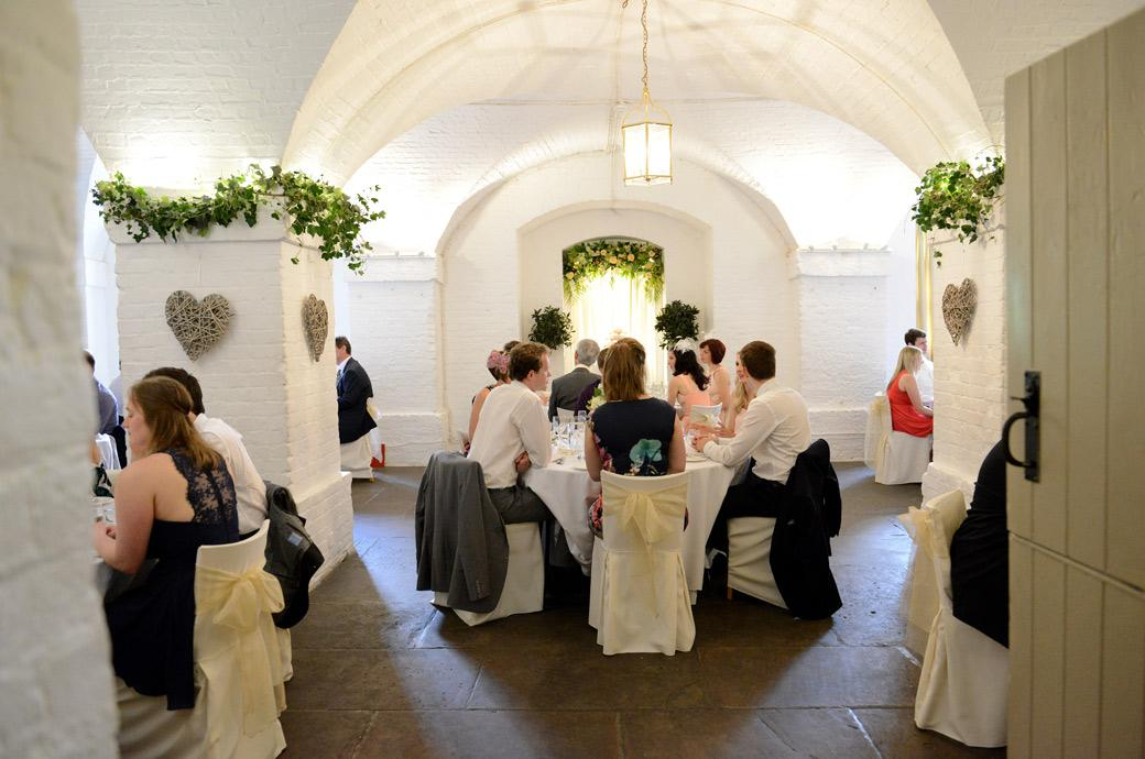 Through the door wedding picture of guests seated awaiting the first course of the wedding breakfast captured at the magnificent Clandon Park in Guildford Surrey