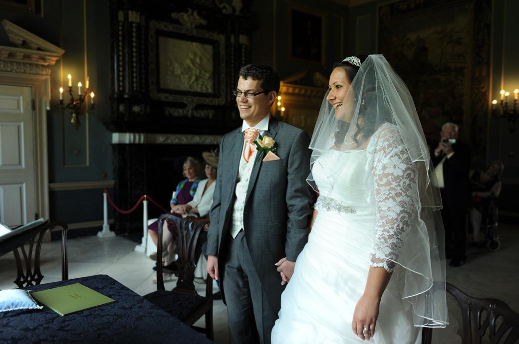 Happy couple smile with joy as they stand hand in hand in this delightful wedding photo captured in the Tapestry Room at Clandon Park by Surrey Lane wedding photography