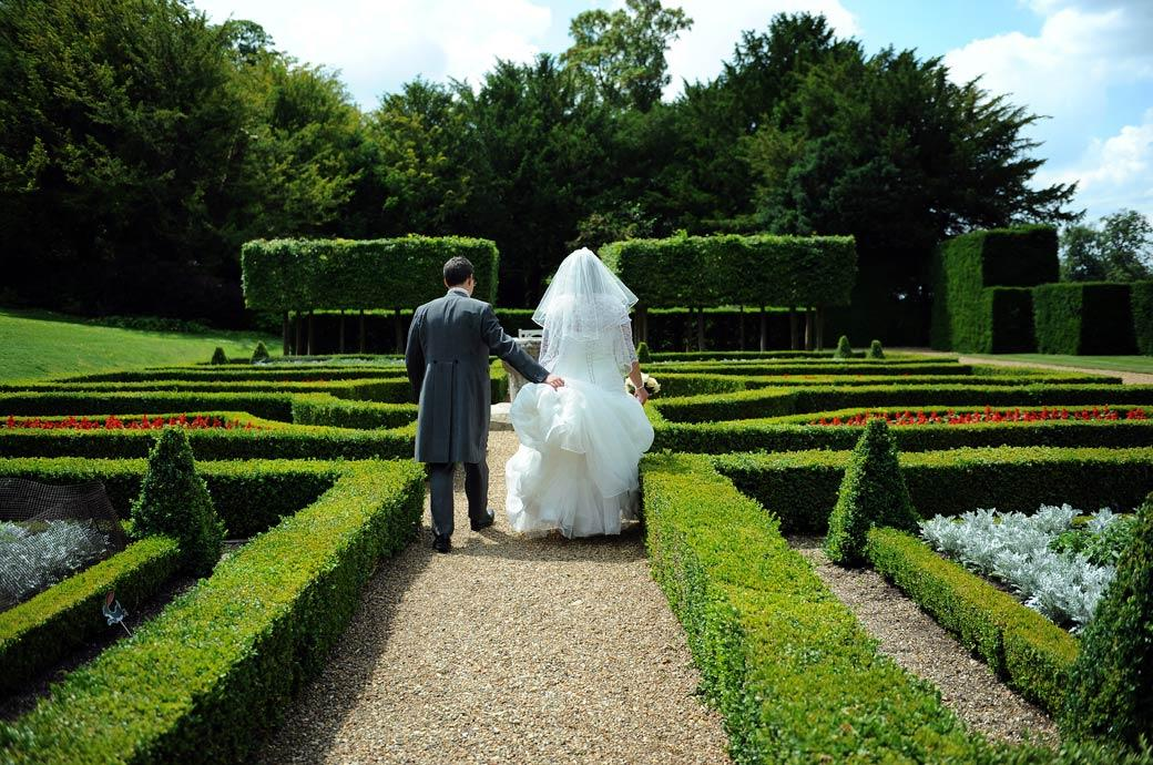 Groom holds up his Bride's dress as they walk through the colourful formal parterre garden in this Clandon Park wedding photo by Surrey Lane wedding photography
