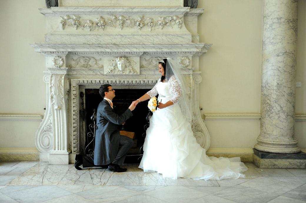 Fun and romance captured in this wedding photograph of the Groom kneeling before his new wife in front of an ornate fireplace at surrey wedding venue Clandon Park in the Marble Hall