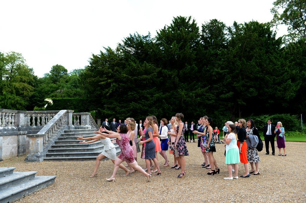 Great action wedding photo of the ladies stretching out to catch the Bride's wedding flower bouquet at Clandon Park a stunning Surrey wedding venue near Guildford