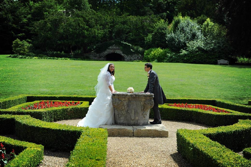 Groom looks over to his wife as they lean on the giant stone urn in this wedding picture taken by surrey lane wedding photography in the Clandon Park parterre garden