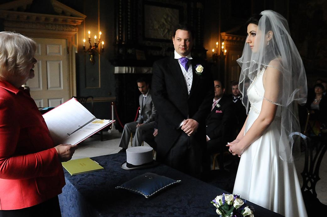 Bride and Groom listen attentively to the Registrar as the marriage ceremony begins in the Tapestry Room at the stunning Surrey wedding venue Clandon Park
