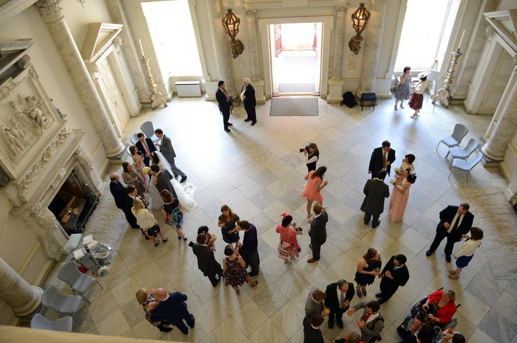 Ariel wedding photo taken from the balcony looking down onto the post marriage celebrations in the wonderful Marble Hall at Surrey wedding venue Clandon Park