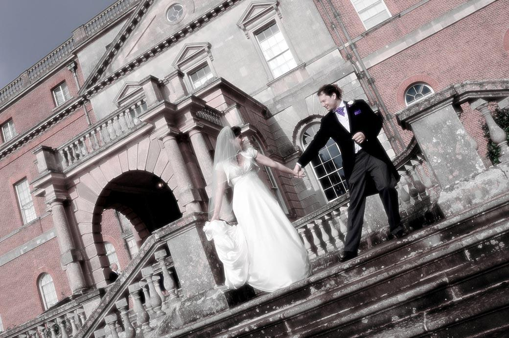 Newly-weds dance theatrically on the grand entrance steps at Clandon Park Surrey wedding venue taken by the wedding photographers at Surrey Lane