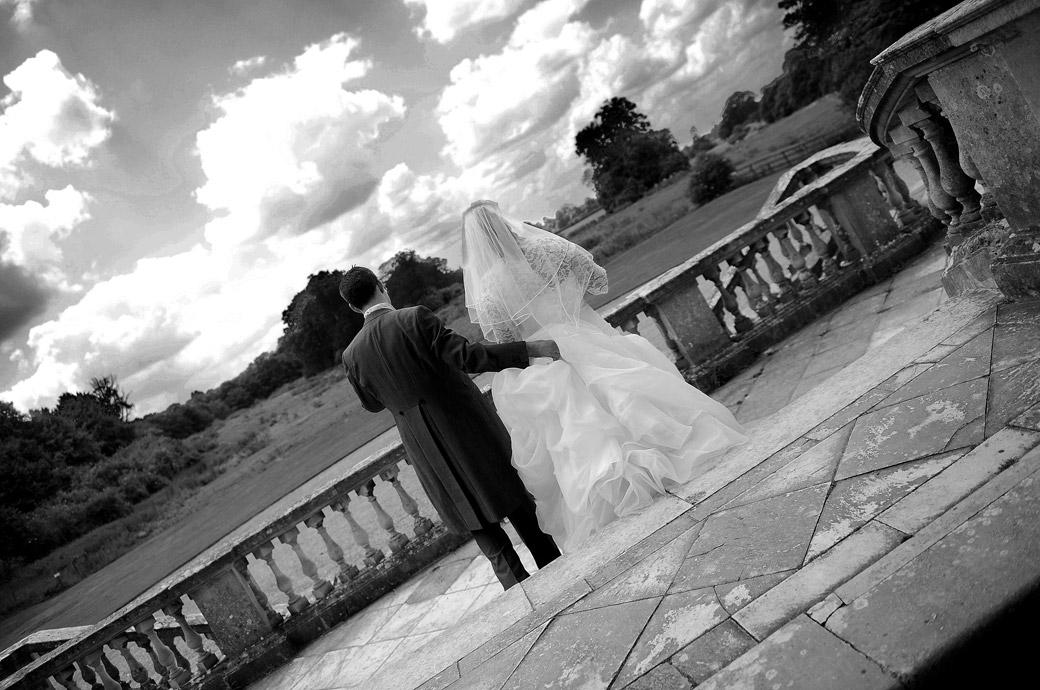 Romantic wedding photo of the newly-weds standing looking over the balustrade towards the beautiful horizon by Surrey Lane wedding photography at Clandon Park in Guildford