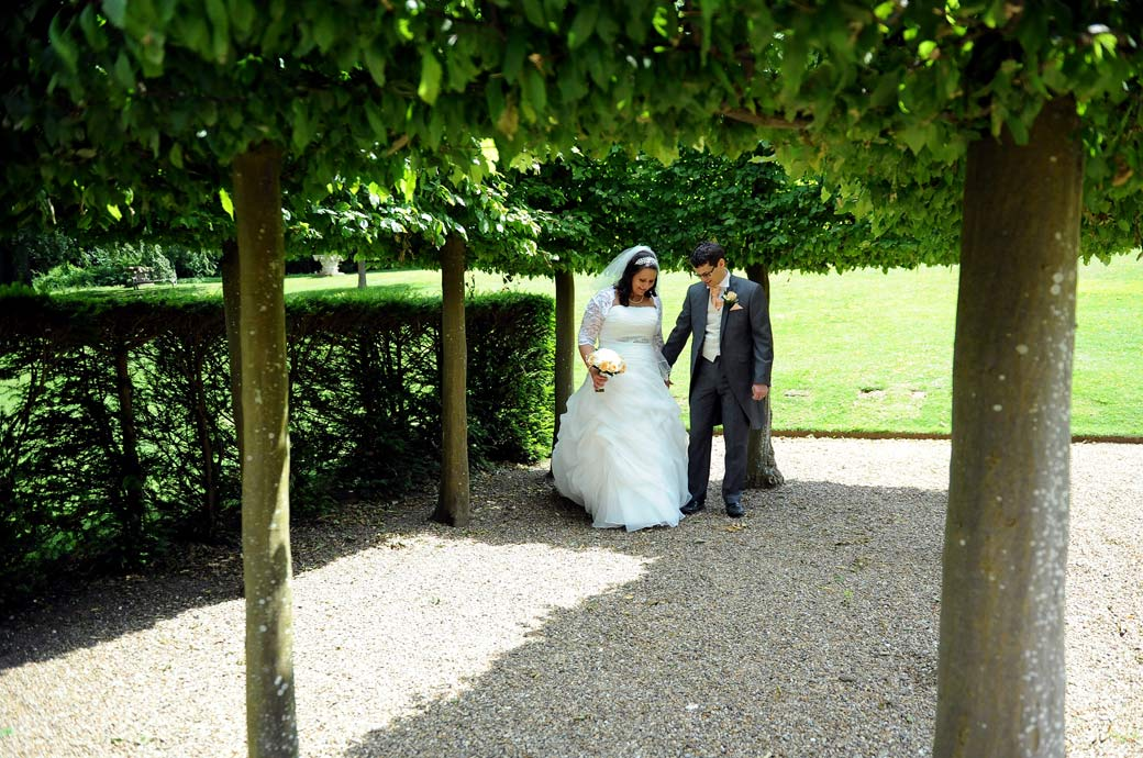 Married couple share a little moment as they walk under the shade of the trees in this wedding picture taken at Surrey wedding venue Clandon Park as they enter the parterre garden