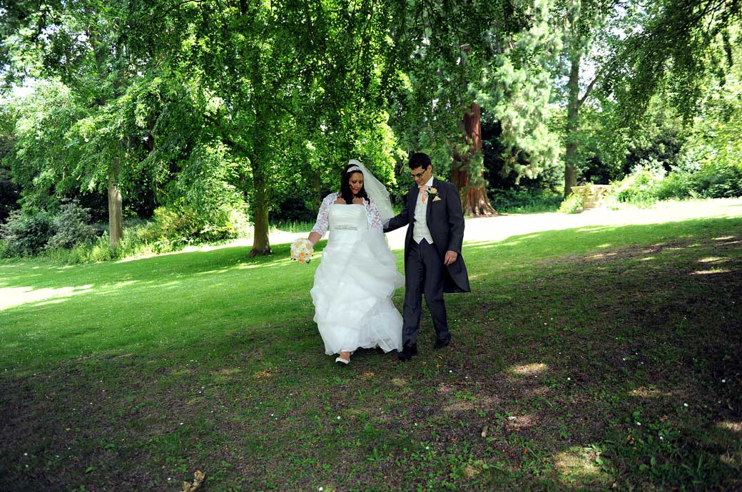 The Groom helps his wife as they walk under the trees in this wedding photograph captured by Surrey Lane wedding photographers in the lovely Clandon Park grounds