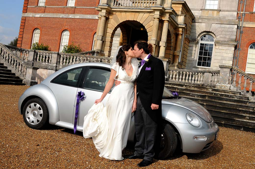 Bride and Groom at the stunning Surrey wedding venue Clandon Park Guildford have a passionate kiss in front of their wedding car on the gravel drive