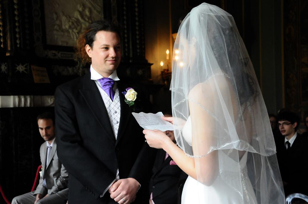 A beautifully intimate wedding photograph of the Bride reading her vows to a happy Groom by Surrey Lane wedding photography at Clandon Park Surrey