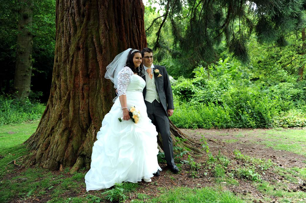 Standing in front of the giant Redwood tree out of the sun in this relaxed wedding picture taken in the tranquil gardens at Clandon Park a stunning marriage venue in Surrey