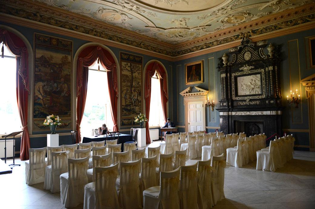 Registrars preparing for the marriage ceremony in this discrete wedding photo captured by Surrey Lane wedding photography at Clandon Park in the beautiful Tapestry Room