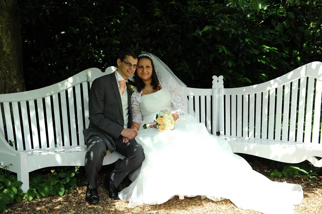 Relaxing together on the long white garden seat in this wedding picture of the newly-weds taken in the gardens at Clandon Park a wonderfully grand Surrey wedding venue