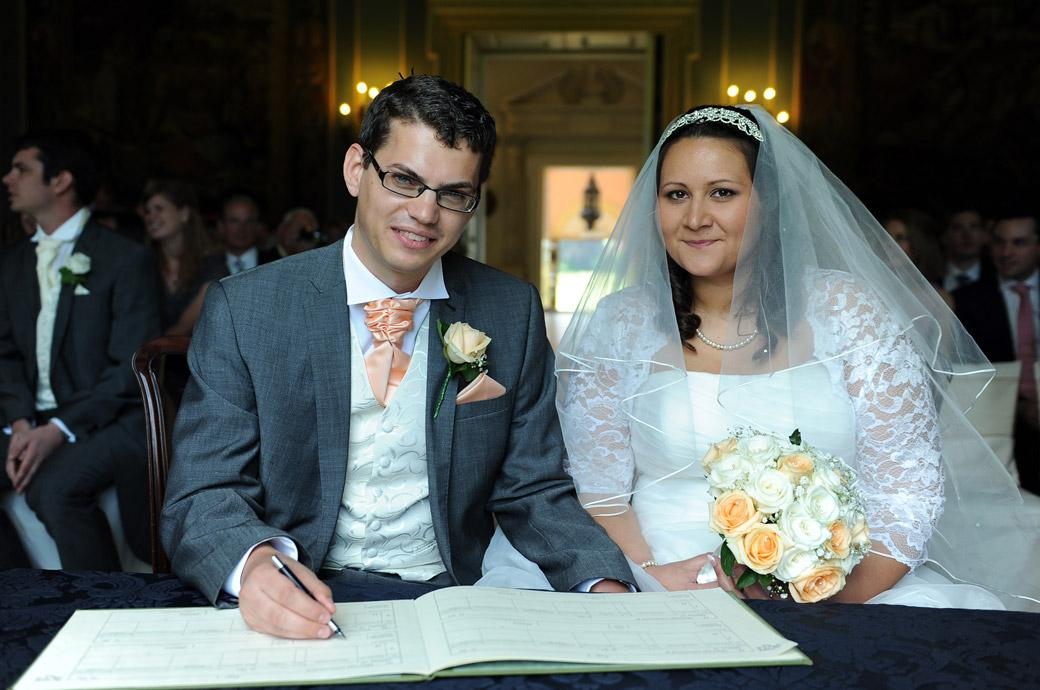 A relieved and happy couple pose for the photographer in this signing the marriage register wedding photograph taken in the Tapestry Room at Clandon Park in Guildford Surrey