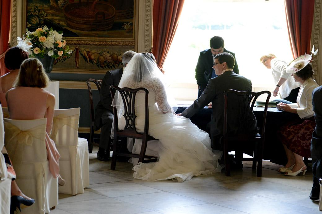 Groom looks over to his new wife in this wedding picture captured as they sit before the registrar ready to sign the marriage register at Surrey wedding venue Clandon Park Guildford