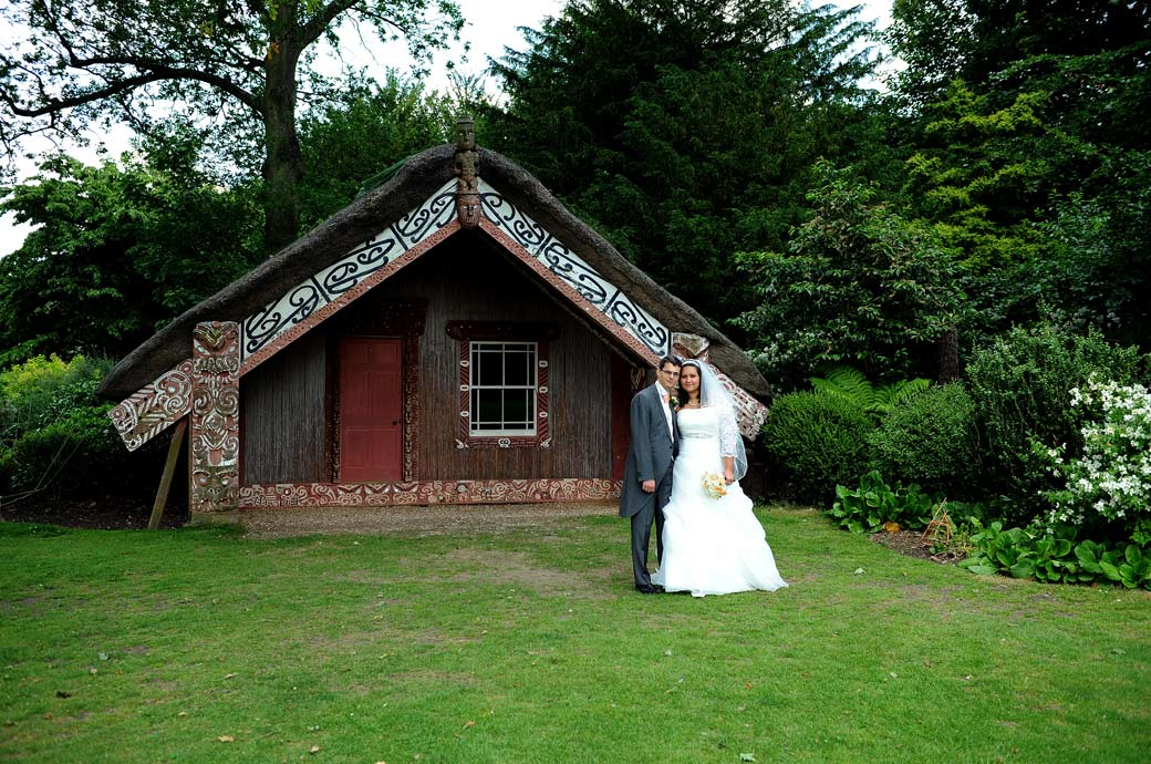 Heads together as the newly-wed couple pose in front of the Maori meeting house in this Clandon Park wedding photograph by Surrey Lane wedding photography