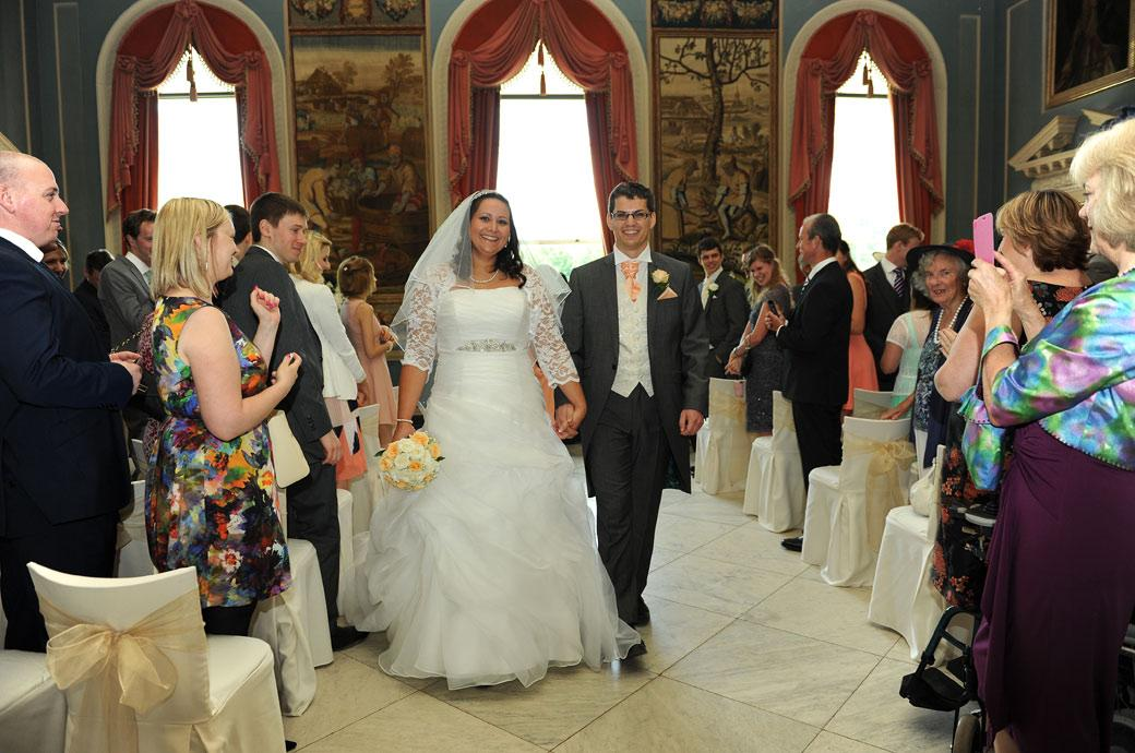 Beaming husband and wife walk down the aisle in this wedding photograph taken in the Tapestry Room accompanied by much applause at Clandon Park near Guildford in Surrey