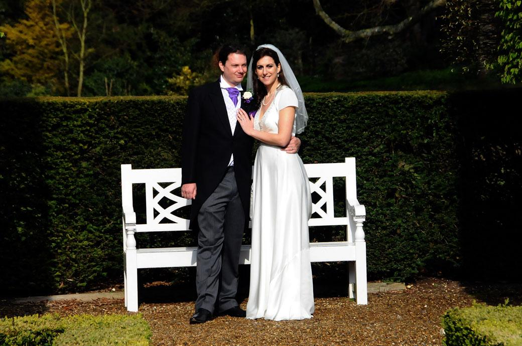 Content newly-weds stand together as husband and wife at Surrey wedding venue Clandon Park in the beautiful and calming Parterre Garden