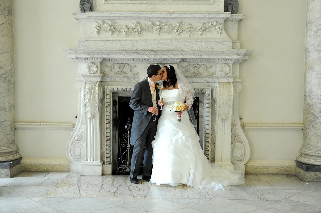 A romantic kiss in front of an ornate fireplace captured in this wedding picture of the Bride and Groom after being married at Surrey wedding venue Clandon Park in Guildford