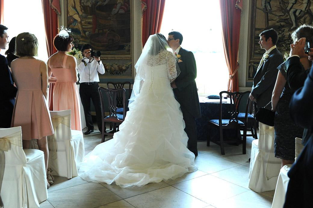 Bride and Groom kiss before the marriage ceremony begins in this romantic wedding picture captured by Surrey lane wedding photogarphers at Clandon Park in the Tapestry Room