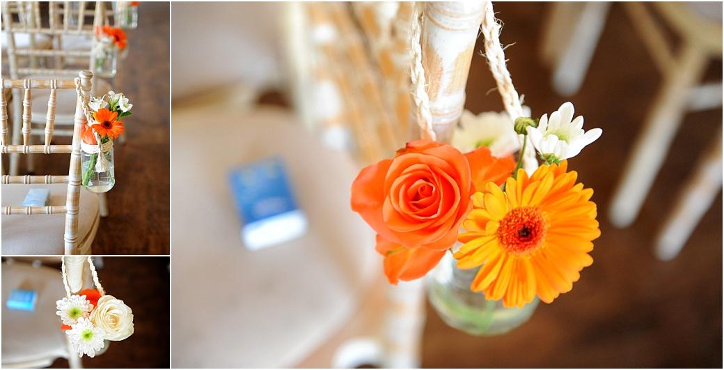 Wedding pictures of cute little jars of bright wedding flowers captured at Clock Barn Hall Godalming in Surrey hung onto the aisle chairs with string in the ceremony room