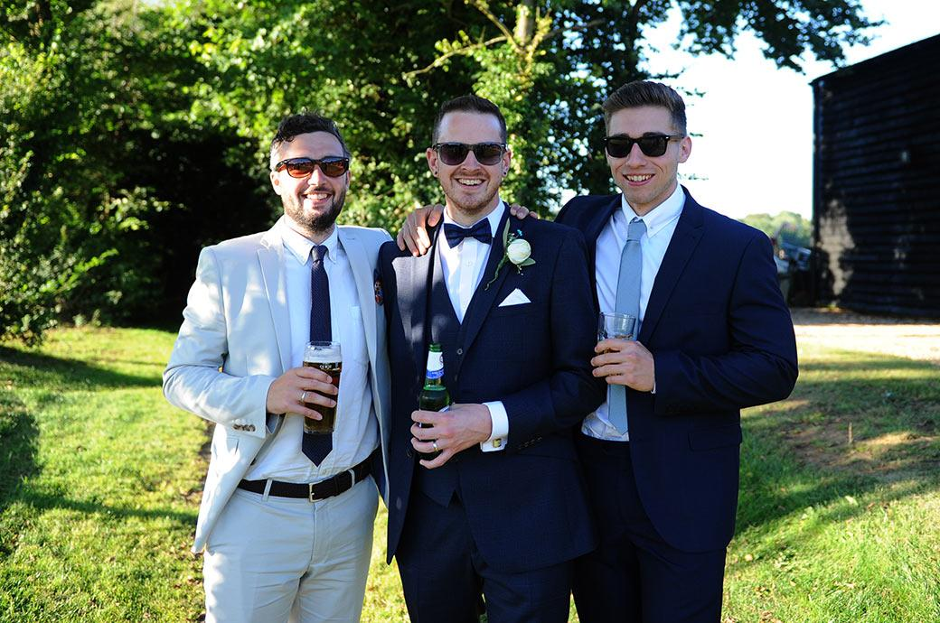 Relaxed groom poses with his friends as they all have a beer under the trees on a hot summer wedding day taken at Clock Barn Hall by a Surrey Lane wedding photographer