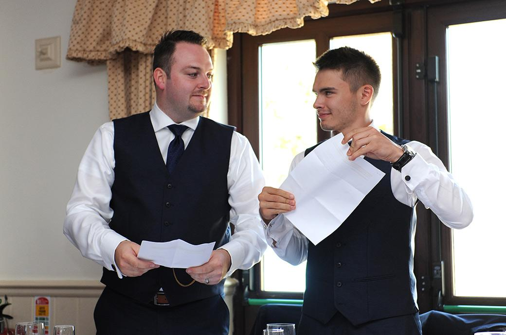 Best men give knowing glances during their fun and entertaining wedding speech routine at the lovely rural Clock Barn Hall wedding venue in the Surrey countryside
