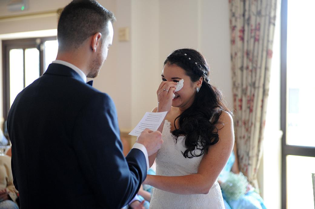 Bride wipes the tears of emotion as her Groom reads out his personal marriage vows during at the lovely wedding venue Clock Barn Hall in leafy Surrey