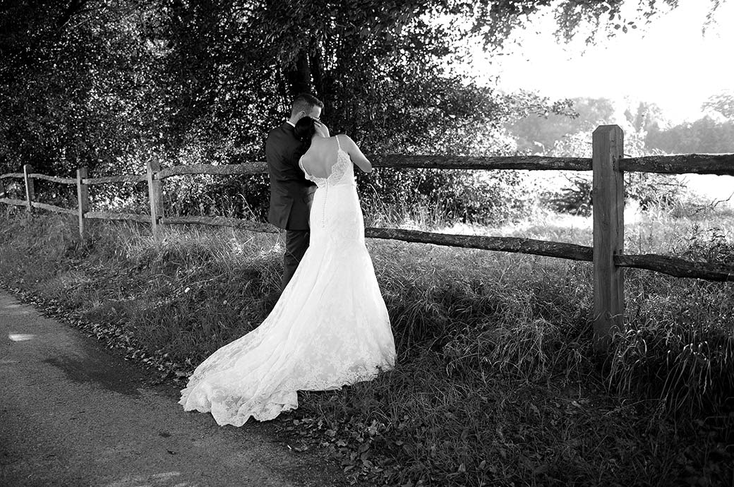 Bride rests her head on her Groom's shoulder as they stand by a fence on the lane looking over the lovely Surrey countryside in this romantic Clock Barn Hall wedding photograph