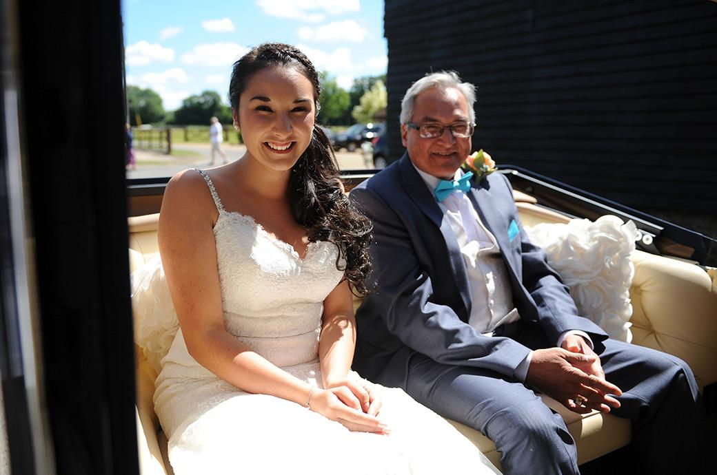 An excited Bride is captured by a Surrey Lane wedding photographer as she arrives at Clock Barn Hall Godalming in a classic open top Regent Landaulette wedding car with her father