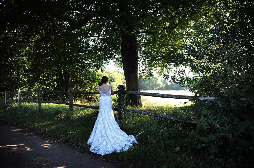 Wedding picture of a bride in her beautiful dress standing on a country lane in Surrey at Clock Barn Hall wedding venue in Godalming looking out over the fields