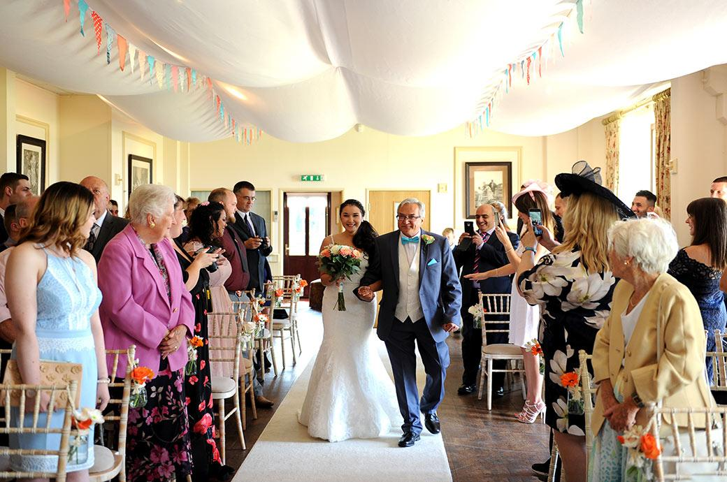 Wedding picture of a happy smiling Bride on her smiling father's arm captured at Surrey wedding venue Clock Barn Hall Godalming as they walk down the aisle