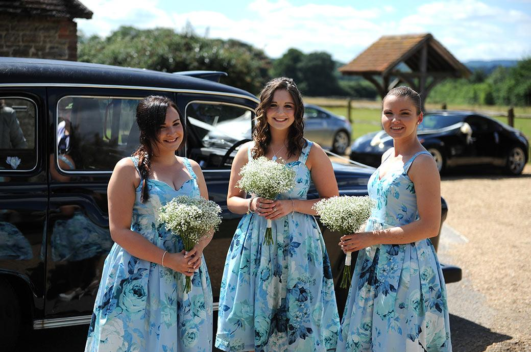 Smiling bridesmaids holding their posies resplendent  in their lovely blue floral dresses at Clock Barn Hall Godalming Surrey as they await the arrival of the Bride